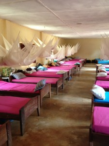 Photo of The Girl's Dorm at Kabanga Protectorate Center, with pink and blue sheets, and bug netting over the beds